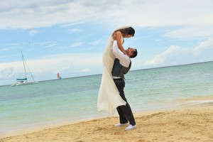 Austin lifts Christine into the air on the beach